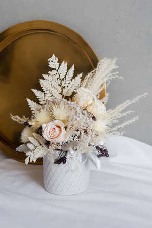 Stylish composition of preserved flowers and dried flowers in a light color scheme on the background of a golden tray. Photo of a bouquet with roses in a vase. Color close-up photo. 免版税图像