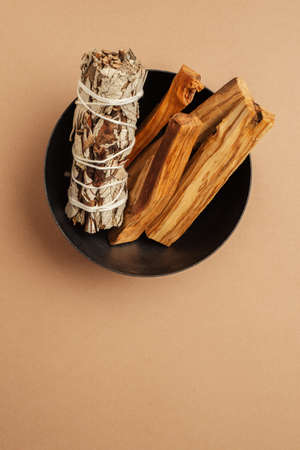 Set of incense for fumigation. White sage sprigs and Palo Santo sticks tied in bunch in metal bowl. View from above. Organic holy tree incense from Latin America. Close-up color photo.