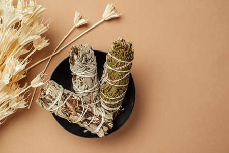 Set of incense for fumigation of premises. Branches of white sage tied in a bunch and dried flowers of Nigella. View from above. Organic holy plant incense from Latin America. Close-up color photo.