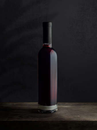 A bottle of red wine, on a wooden empty tabletop against a dark wall background. Wine bottle mockup.