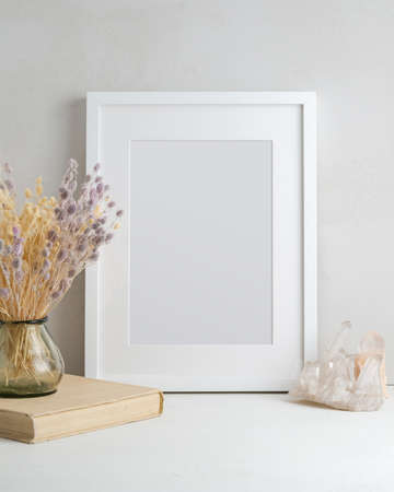 Empty white frame, glass vase with dried flowers, book, and natural crystal in a light interior. Mockup poster with place for your design. 免版税图像