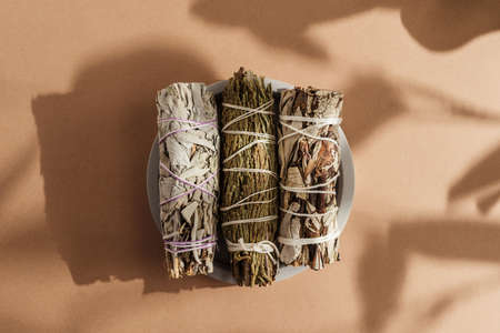 White sage, cedar, yerba santa tied in a bunch on a concrete plate. Set of incense for fumigation, beautifully lit by sunlight. Top view. Close-up color photo. Background with shadow.