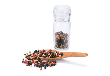 colored pepper peppercorns in wooden scoop and jar on isolated on white background.