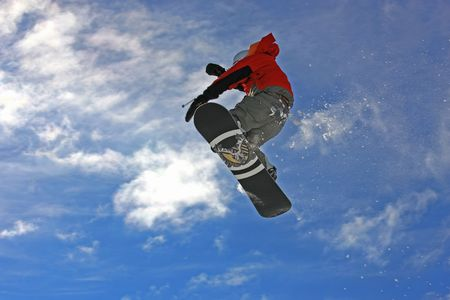 Young snowboarder jumping high over the mountains