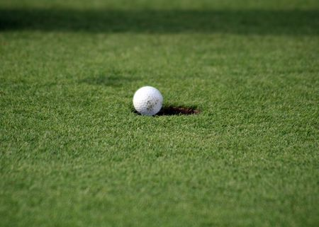 Close view of a golfball just falling in the hole