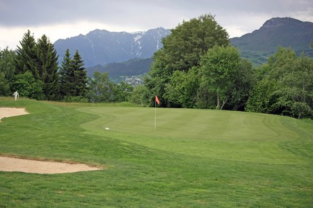 Golf green in front of a mountain scenery