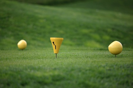 Close view of two yellow balls on a tee in front of a green background Stock Photo