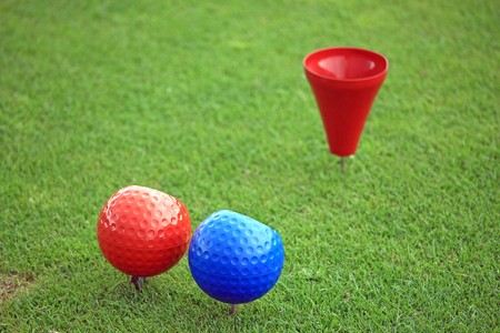 Close view of a red and a blue ball on a tee with a red tee cup