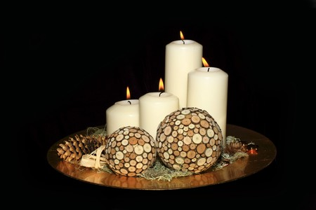 Original advent wreath with four burning candles isolated on a black background