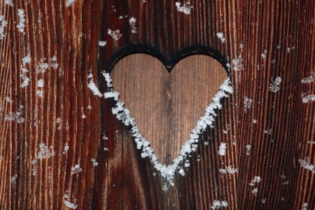Close view of a wooden background with a heart cut out