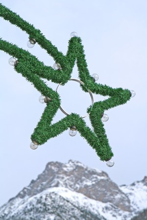 Close view of a christmas illumination forming a star in front of a mountain scenery