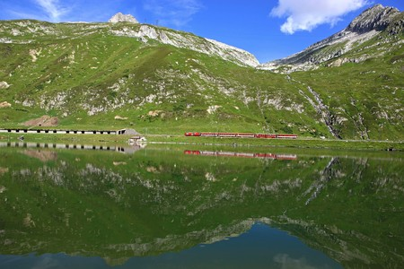 Lake in front of a red train and a wonderful mountain scenery