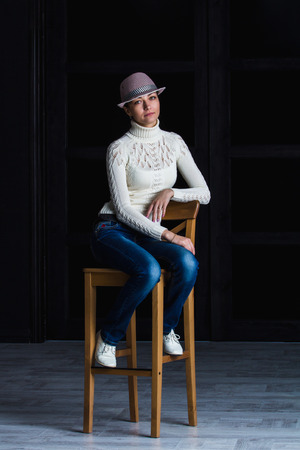 bar stool: girl in a hat sitting on a bar stool