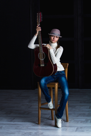 dupe: girl in a hat with a guitar sitting on a bar stool Stock Photo