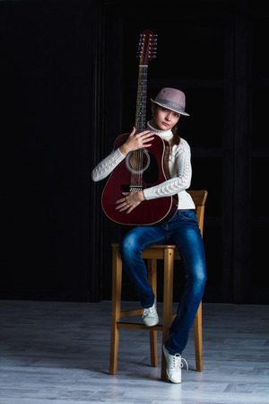 bar stool: girl in a hat with a guitar sitting on a bar stool Stock Photo