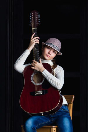 muff: girl in a hat with a guitar sitting on a bar stool Stock Photo