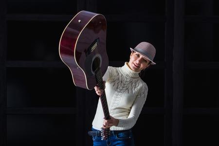 muff: girl in the hat brandishing a guitar Stock Photo