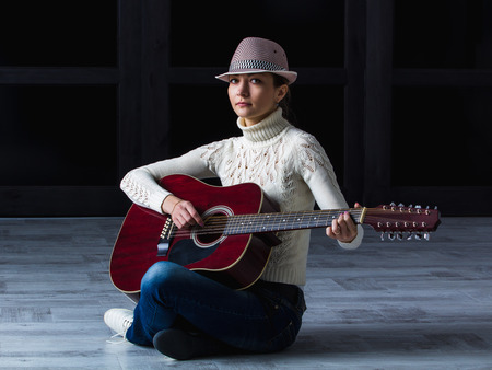 muff: girl in a hat with an acoustic guitar sitting on the floor Stock Photo