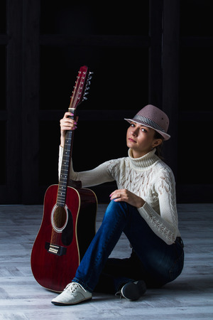 dupe: girl in a hat with an acoustic guitar sitting on the floor Stock Photo