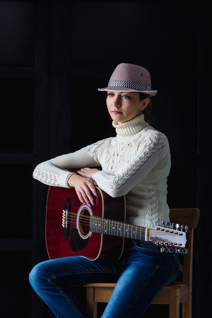 25 30: girl in a hat with a guitar sitting on a bar stool Stock Photo