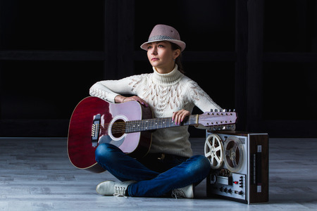 25 30: girl with an acoustic guitar sitting around an old tape recorder