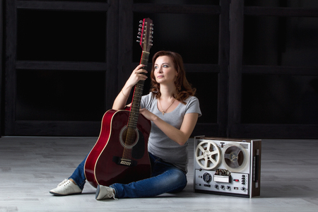 35 40: girl with an acoustic guitar sitting around an old tape recorder