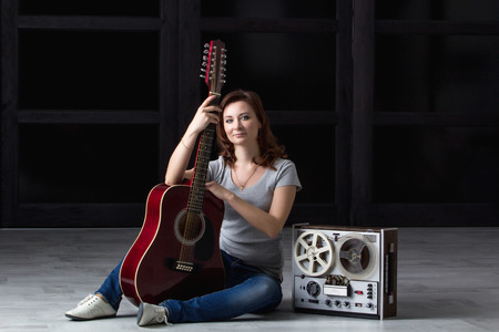 tape recorder: girl with an acoustic guitar sitting around an old tape recorder