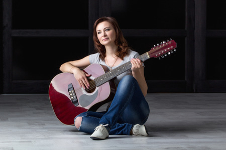 35 40: girl in a hat with an acoustic guitar sitting on the floor Stock Photo