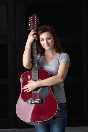 lass: girl in a hat with a guitar sitting on a bar stool Stock Photo