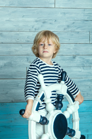 earnest: child standing and holding a steering wheel Stock Photo