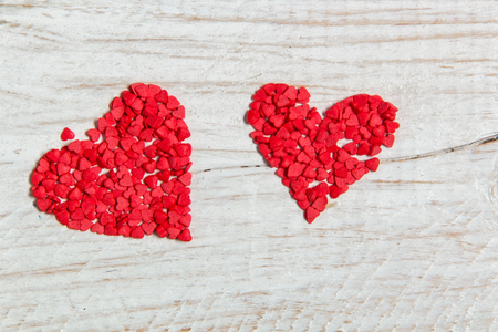 sweetmeats: candy in the form of red hearts lie on the wood Stock Photo