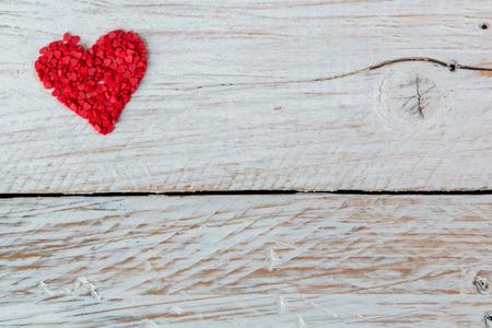 Süßigkeiten in Form von roten Herzen liegen auf dem Holz Standard-Bild - 51975726
