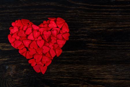 Süßigkeiten in Form von roten Herzen liegen auf dem Holz Standard-Bild - 51975731