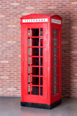 cabina telefonica: cabina de tel�fono roja en el fondo de un ladrillo viejo Foto de archivo