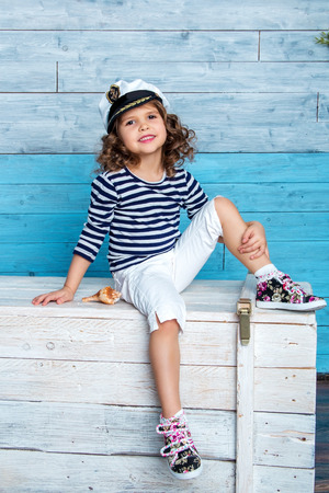 striped vest: child in striped vest sits on the dower chest