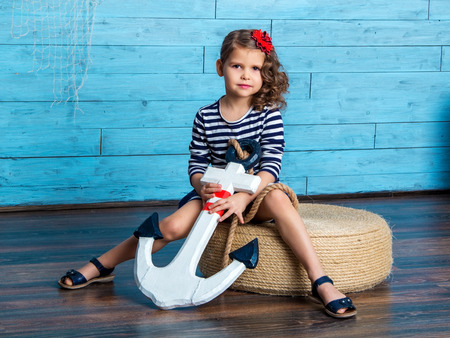 pouf: child sitting on pouf and holds anchor