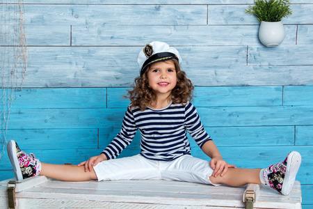 striped vest: child in striped vest sits on a splits