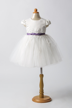habiliment: Baby white dress on a mannequin, light gray background