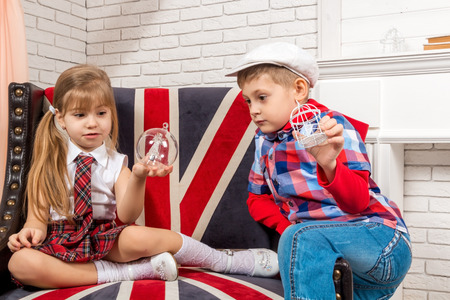 british girl: girl and boy sitting on a chair with a British flag Stock Photo
