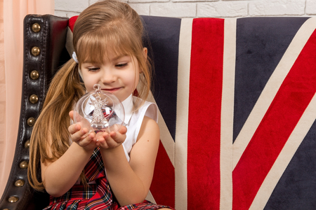 british girl: girl sitting on chair with a British flag, closeup