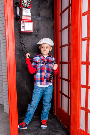 phone cord: Boy in cap standing in a red telephone booth and holding a phone cord