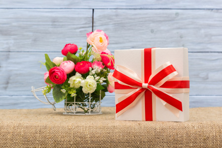 pledge: gift and a vase with flowers, closeup Stock Photo