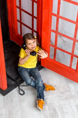 cabina telefono: niña que se sienta en la cabina telefónica y agitando la mano Foto de archivo