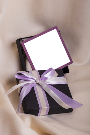 donative: Black gift with a purple bow, closeup Stock Photo
