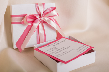 donative: White gift with a pink bow, closeup Stock Photo