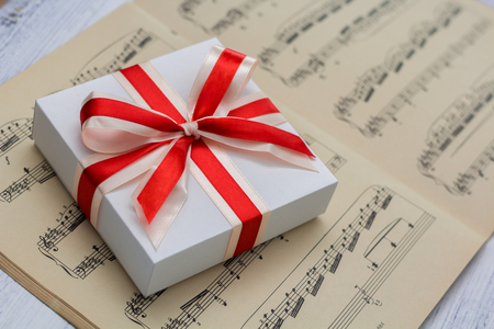 notes: gift with red bow lying on sheet music, closeup