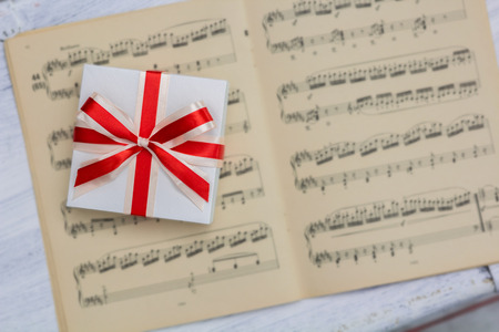 sheet music: gift with red bow lying on sheet music, view from above Stock Photo