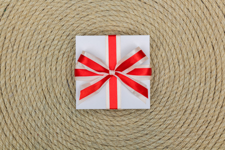 donative: gift lying on background made of rope, closeup