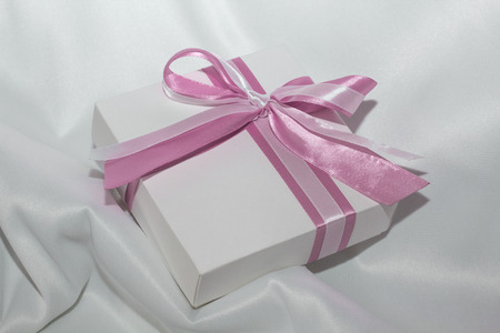 pledge: gift with pink ribbon lies on a white cloth