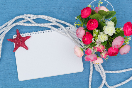 lashing: notebook, starfish and flowers on blue canvas, view from above